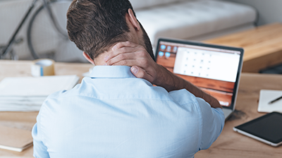 Man sitting at desk stressfully looking down at laptop with hand on his neck.
