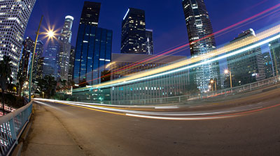 A road with light trails, city skyline in the background