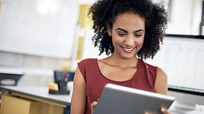 A woman smiling while using a tablet