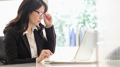 Woman dressed in business attire sitting at desk using a laptop while holding the corner of her glasses.