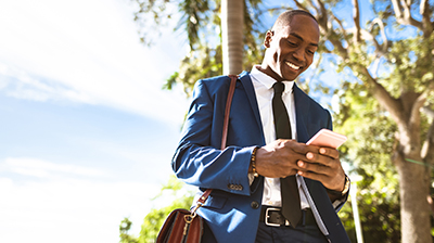 Man in business attire standing outside smiling and looking down at phone.