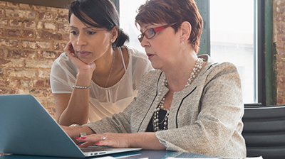 Two women in casual attire looking down at an open laptop in front of them. One woman is standing next to the other who is sitting.